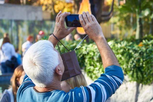 Hommes Sur La Rue Photographiant Avec Un Téléphone Mobile, Le Fond Est La Ville Estompée Photo Premium