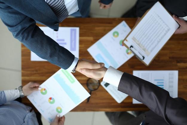 Des Hommes Se Serrent La Main Sur La Table Avec Des Rapports. Photo Premium