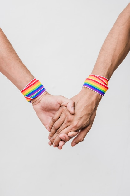 Hommes se tenant la main avec des cassettes aux couleurs lgbt Photo gratuit