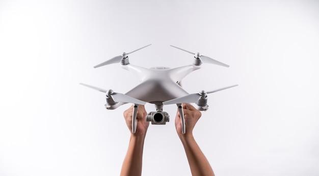 Les hommes tiennent le drone décollent avec la caméra sur le fond blanc, isolé. Photo Premium