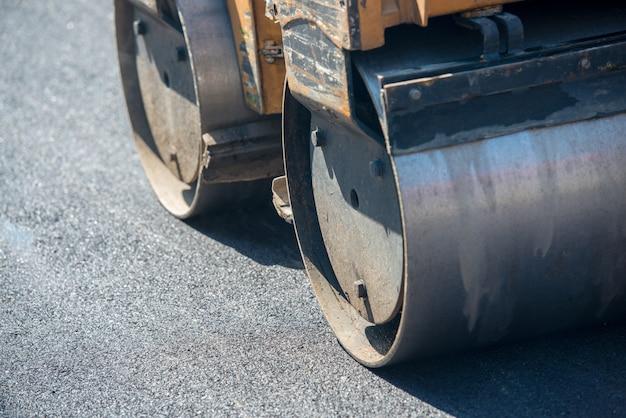 Hommes travaillant sur une nouvelle rue en mettant un nouvel asphalte Photo Premium