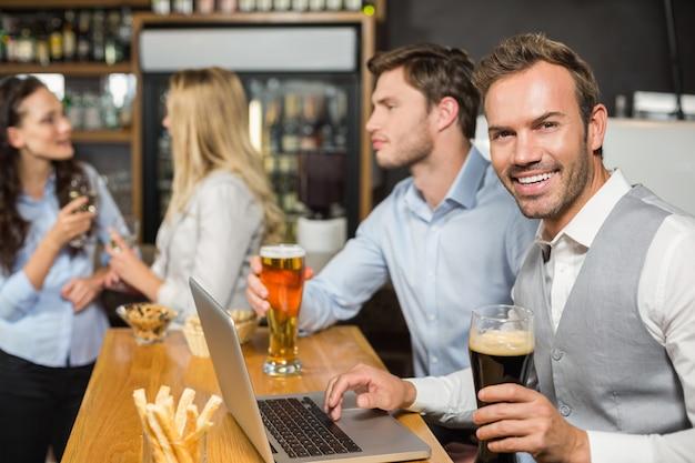 Hommes travaillant sur un ordinateur portable pendant que les femmes parlent derrière Photo Premium