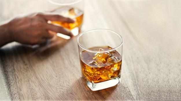 Des hommes et des verres de whisky boivent une boisson alcoolisée ensemble entre amis au comptoir Photo Premium