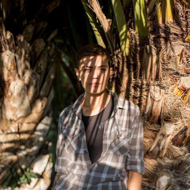 Homosexuel debout dans l'ombre près de l'arbre Photo gratuit