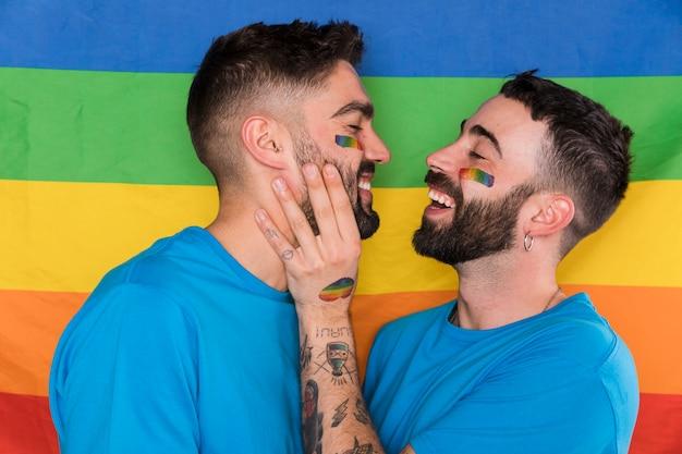 Homosexuel, homme, toucher, petit ami, visage, sur, drapeau multicolore, lgbt Photo gratuit