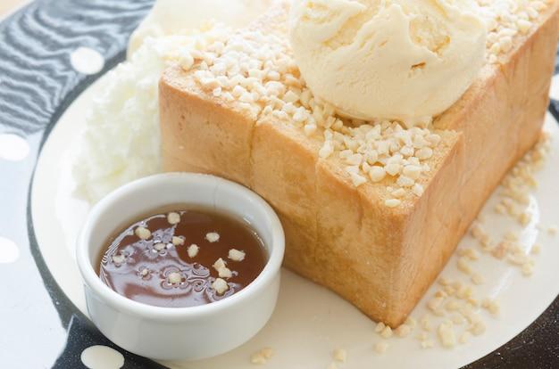 Honey toast, composé de pain garni de miel et de crème glacée Photo Premium