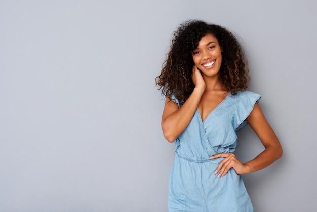 Horizontale belle jeune femme noire souriant sur fond gris Photo Premium