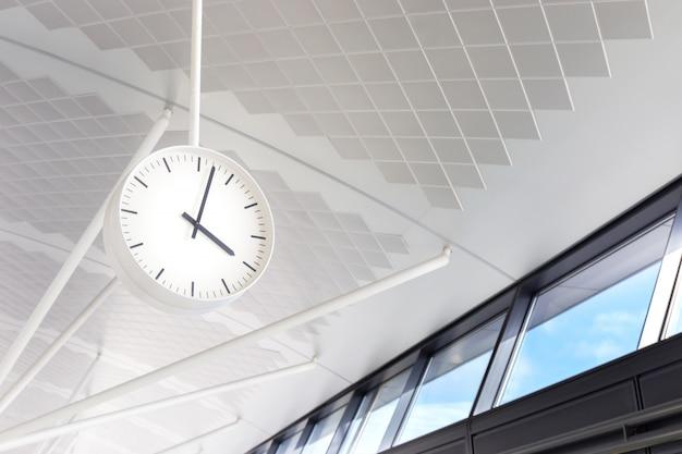 Horloge blanche accrochée au sol entre le hall des départs et des arrivées, terminal de l'aéroport international Photo Premium