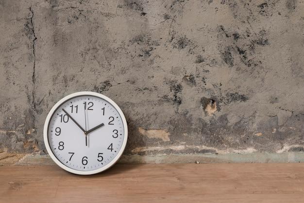Horloge sur un bureau en bois contre un mur patiné Photo gratuit