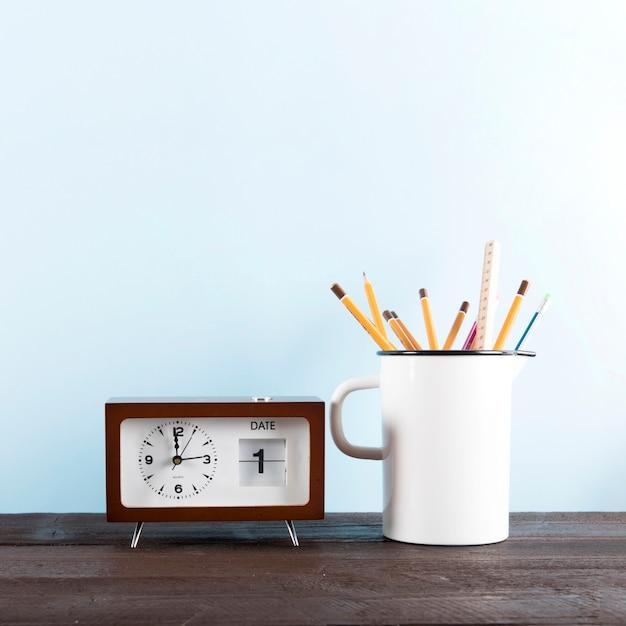 Horloge avec calendrier près de la tasse avec des crayons Photo gratuit