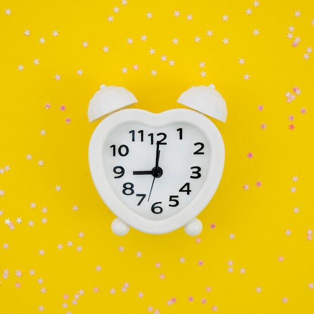 Horloge En Forme De Coeur Blanc Sur Fond Jaune Photo gratuit