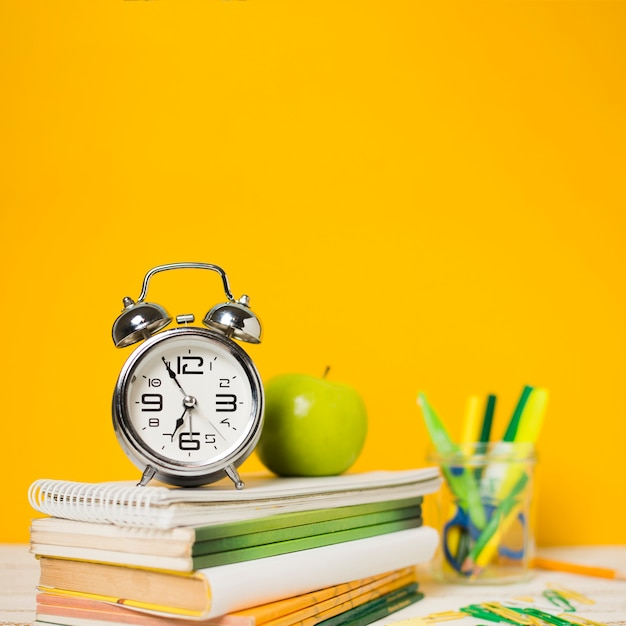Horloge et livres avec fond défocalisé Photo gratuit