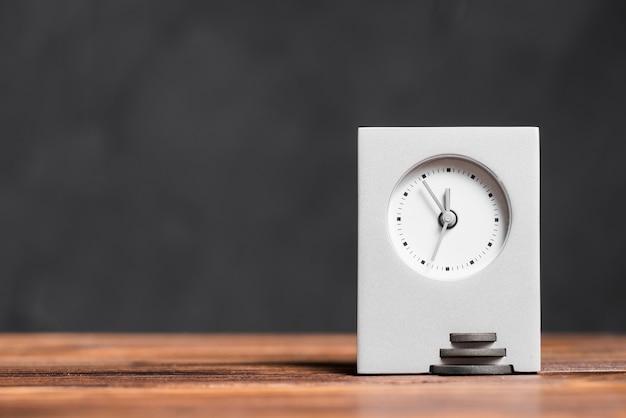 Horloge rectangulaire moderne sur un bureau en bois texturé sur fond noir Photo gratuit