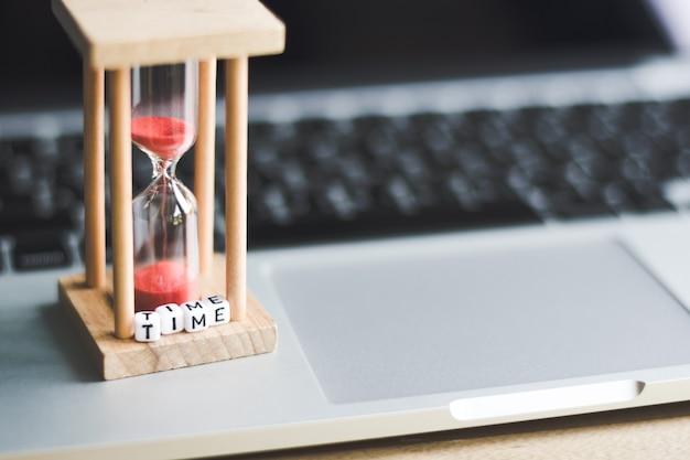 Horloge de sable sur ordinateur portable avec Photo Premium