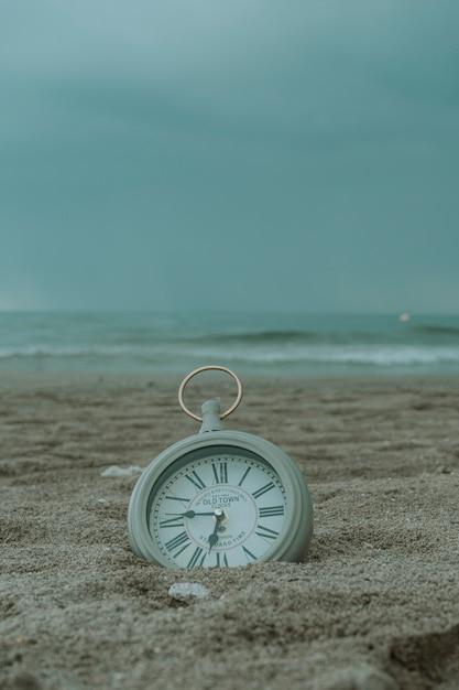 Horloge sur le sable de la plage Photo Premium