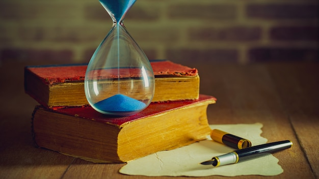 Horloge de sable avec des vieux livres et un stylo avec une carte en papier sur la table en bois. Photo Premium