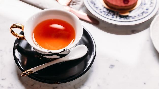 Hot apple tea servi dans une tasse en porcelaine vintagr avec un gâteau aux mousses sur une table en marbre. Photo Premium