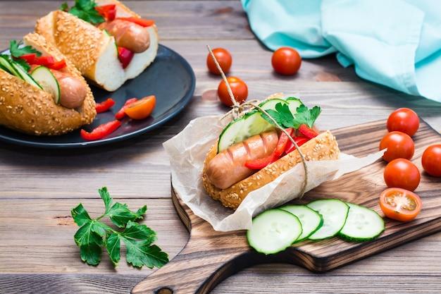 Hot-dog appétissant fait de saucisses frites, petits pains et légumes frais, enveloppé dans du papier sulfurisé sur une planche à découper sur une table en bois Photo Premium