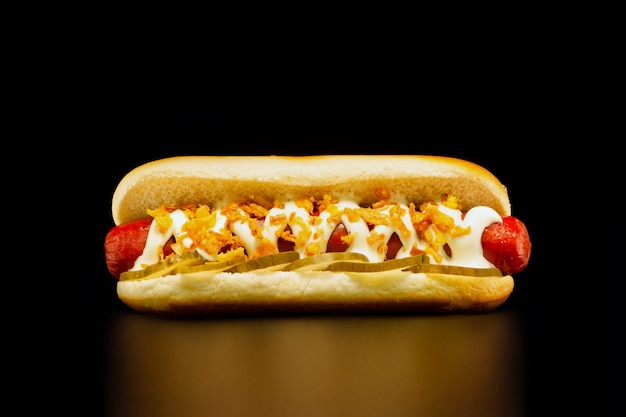 Hot-dog Appétissant Avec Saucisse De Bœuf Grillée, Cornichons, Mayonnaise Et Oignons Frits Sur Fond Noir Photo Premium