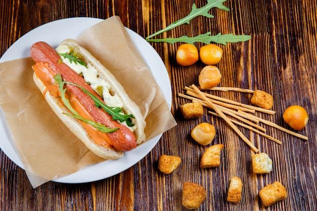 Hot dog avec des cornichons et de la roquette et des collations à la bière fumée Photo Premium