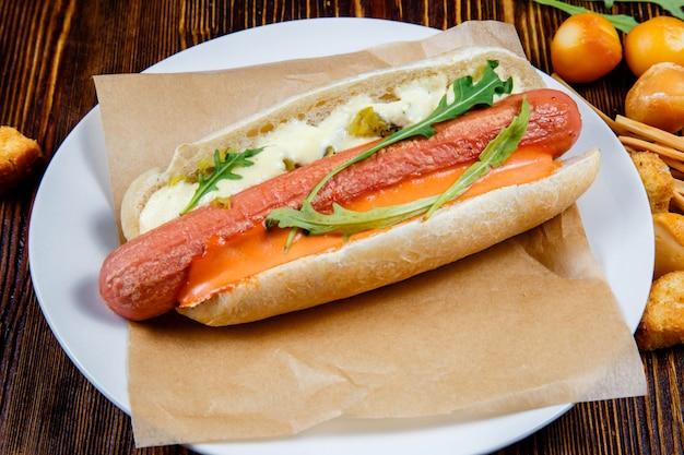Hot-dog avec des cornichons et de la roquette et des collations à la bière fumée. Photo Premium