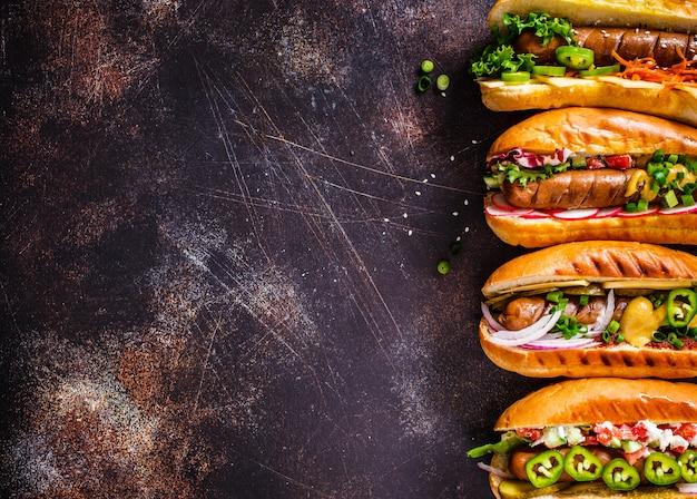 Hot Dogs Avec Différentes Garnitures Sur Fond Sombre, Espace Copie, Vue De Dessus, Photo Premium