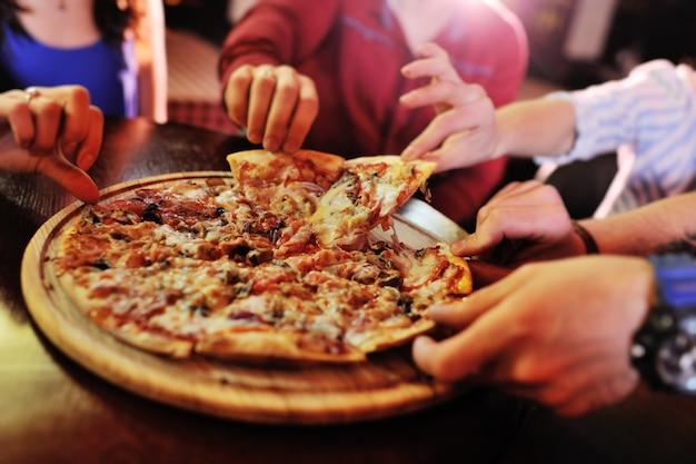 Hot pizza gros plan sur une table à l'arrière-plan d'un groupe ou d'une société entre amis Photo Premium