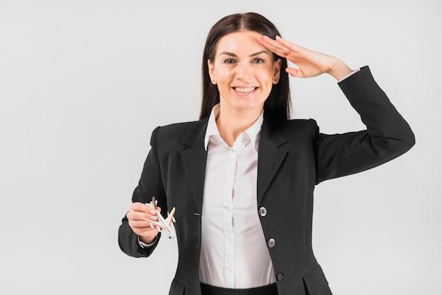 Hôtesse de l'air avec l'avion saluant Photo gratuit