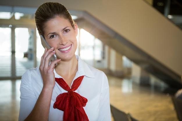 Hôtesse De L'air Heureux Parlant Sur Son Téléphone Mobile Photo gratuit