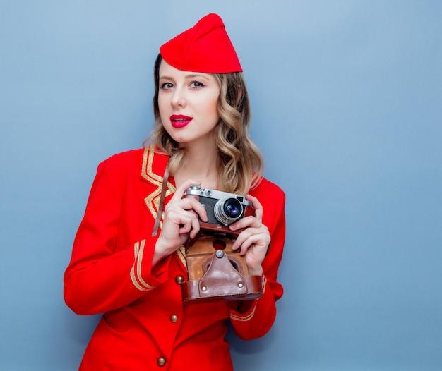 Hôtesse de l'air portant un uniforme rouge avec appareil photo vintage Photo Premium