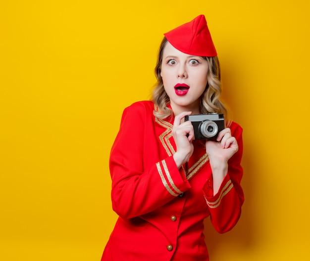 Hôtesse de l'air portant un uniforme rouge avec appareil photo Photo Premium