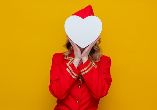 Hôtesse de l'air portant un uniforme rouge avec boîte de gfit de vacances en forme de coeur Photo Premium