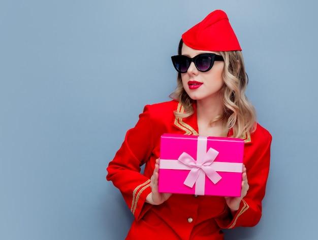 Hôtesse de l'air portant un uniforme rouge avec le conseil cadeau de vacances Photo Premium