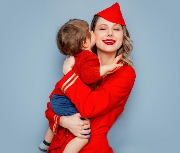 Hôtesse de l'air portant un uniforme rouge avec un enfant sur les mains Photo Premium