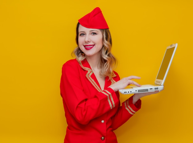 Hôtesse de l'air portant un uniforme rouge avec ordinateur portable Photo Premium