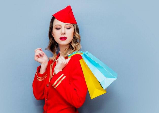 Hôtesse de l'air portant un uniforme rouge avec des sacs à provisions. Photo Premium