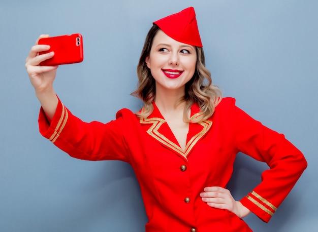 Hôtesse de l'air portant un uniforme rouge avec téléphone portable Photo Premium