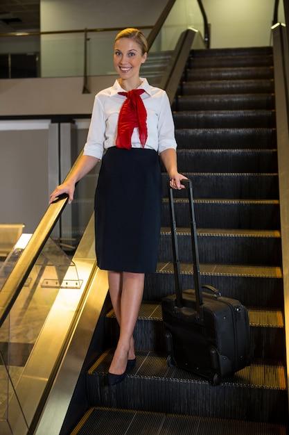 Hôtesse De L'air Avec Sac De Chariot Sur L'escalator Photo gratuit