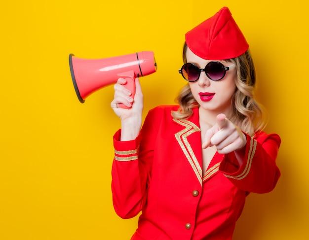 Hôtesse de l'air vintage vêtu de l'uniforme rouge avec mégaphone Photo Premium