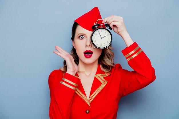 Hôtesse de l'air vintage vêtu de l'uniforme rouge avec réveil Photo Premium