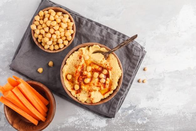 Houmous, bâtonnets de carottes fraîches et pois chiches cuits dans des bols en bois. concept de cuisine végétalienne, fond clair, espace copie, vue de dessus Photo Premium