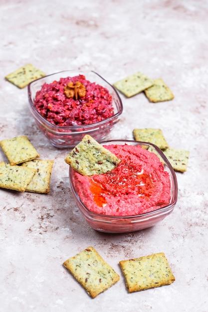 Houmous De Betterave Aux Biscuits Salés Sur Une Surface Claire Photo gratuit