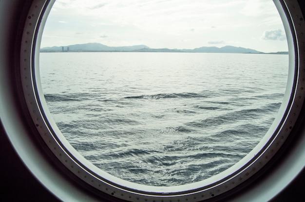 Hublot Rond Sur Un Bateau De Croisière, Vue Intérieure Par La Fenêtre Sur La Côte Et La Mer, Lever Du Soleil Sur La Mer, Gros Plan Photo Premium