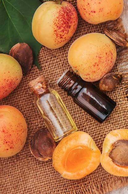 Huile d'abricot dans un petit pot. mise au point sélective. Photo Premium