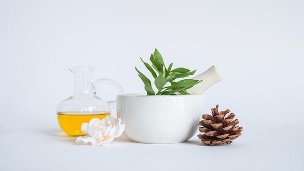 Huile d'aromathérapie au mortier et à la feuille verte naturelle. concept de produit arôme peau beauté spa. Photo Premium