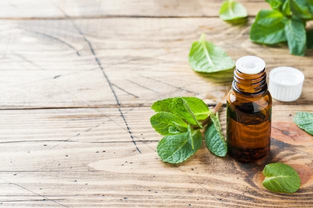 Huile essentielle aromatique à la menthe poivrée sur fond en bois. Photo Premium
