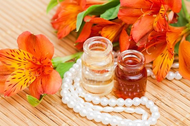 Huile essentielle aromatique en petits flacons en verre, fleurs d'alstroemeria et perles de perles Photo Premium