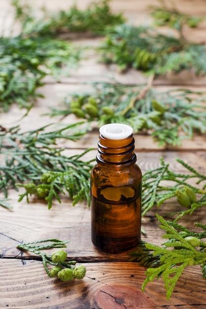 Huile Essentielle D'arôme De Thuya Dans Un Bocal En Verre Sur Une Surface En Bois Photo Premium