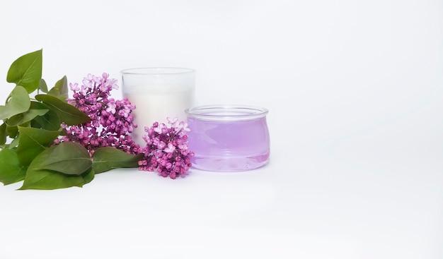 Huile Essentielle, Bougie Aromatique Blanche Et Une Branche De Lilas Sur Fond Blanc. Photo Premium