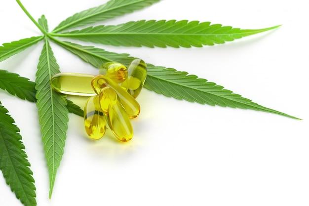 Huile essentielle de cannabis en capsules sur fond blanc. Photo Premium